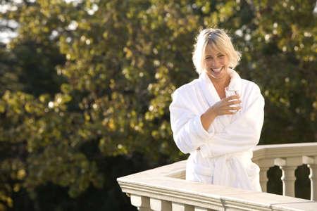 waistup: Woman wearing white bath robe, standing on balcony, smiling, portrait