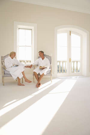 bath robes: Mature couple wearing white bath robes, sitting and holding hands indoors LANG_EVOIMAGES