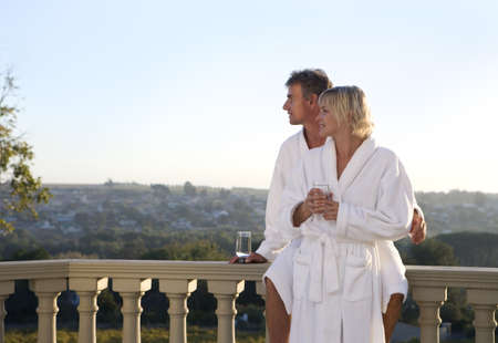 leant: Mature couple wearing white bath robes, standing on balcony, embracing