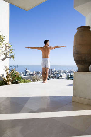 lavishly: Young man standing on balcony, arms outstretched, rear view LANG_EVOIMAGES