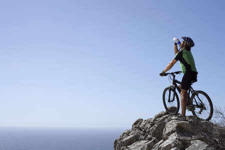 health drink: Male mountain biker sitting on bicycle at edge of rock, looking at horizon over sea, rear view