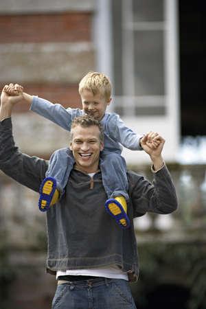 waistup: Padre llevar a hijo (3-5) en los hombros, sonriendo, vista frontal, retrato