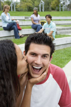western european ethnicity: Teenage couple (17-19) sitting near friends, girl kissing boy on cheek, smiling LANG_EVOIMAGES