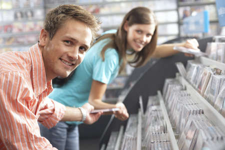record shop: Young man passing CD to woman in record shop, bending down, smiling, side view, portrait