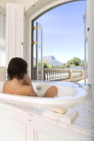 lavishly: Young woman in bath by window, rear view