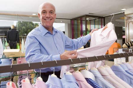 waistup: Hombre maduro en la tienda de ropa, celebraci�n de camisa, sonriente, retrato LANG_EVOIMAGES