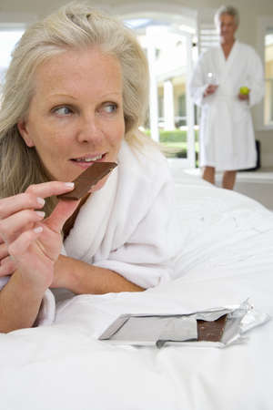 drink me: Mature woman lying on bed, holding piece of chocolate, mature man standing in background LANG_EVOIMAGES