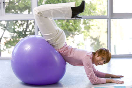 forearms: Young woman on exercise ball, forearms on floor, legs in air, smiling, side view LANG_EVOIMAGES
