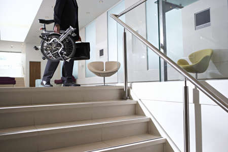 gentleman's: Businessman carrying commuter bicycle and briefcase up steps in lobby, low section, side view