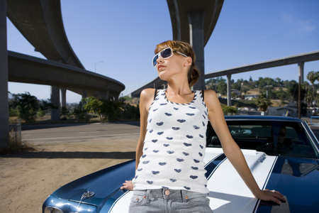 waistup: Young woman on bonnet of car beneath overpass, low angle view LANG_EVOIMAGES