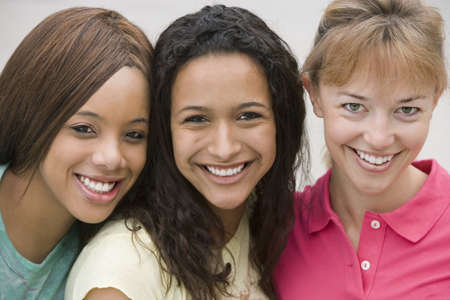 western european ethnicity: Three young women smiling, cheek to cheek, close-up, front view, portrait