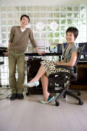 toils: Young man standing by young woman sitting by desk in office, smiling, portrait