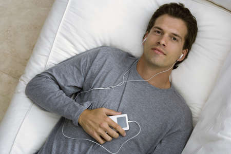 western european ethnicity: Man relaxing on sofa at home, listening to MP3 player, smiling, portrait, overhead view