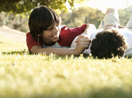 leant: Father and son (10-12) lying on grass in park, smiling, surface level