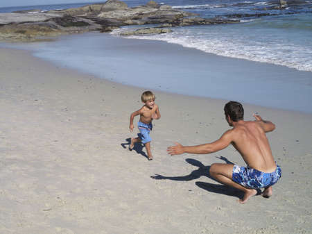 elevated view: Father and son (4-6) playing on beach, boy running into mans arms, smiling, elevated view LANG_EVOIMAGES