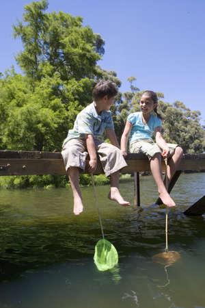 fema: Boy and girl (7-10) sitting on lake jetty, holding fishing nets, smiling
