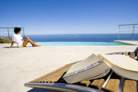 lavishly: Young woman sitting by infinity pool by sea, book on chair in foregorund