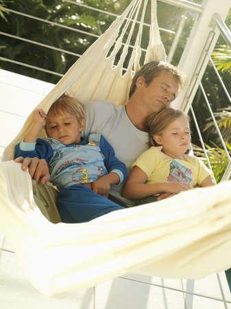 waistup: Padre e hijos (5-8) descansando en una hamaca en el balc�n, para dormir (inclinaci�n)
