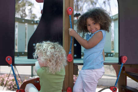 appreciating: Two girls (3-5) playing in adventure playground, smiling