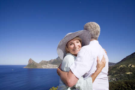 waistup: South Africa, Cape Town, senior couple embracing by sea, smiling, portrait of woman