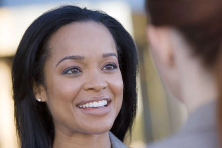 toils: Businesswoman talking to colleague, smiling, close-up (differential focus)