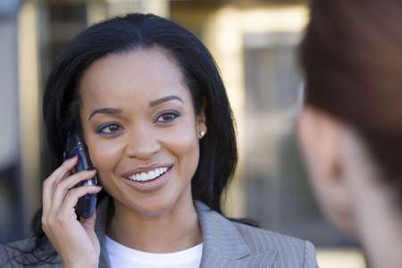 toils: Businesswoman using mobile phone, outdoors, smiling, close-up (differential focus)