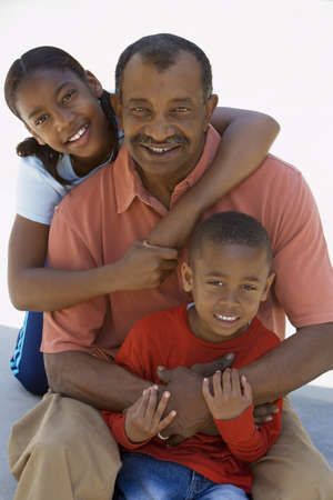 hold ups: Grandfather and grandchildren (6-13) smiling, front view, portrait