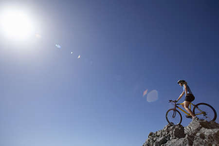 sitt: Female mountain biker sitting on bicycle at edge of rock in sunlight, low angle view (lens flare) LANG_EVOIMAGES