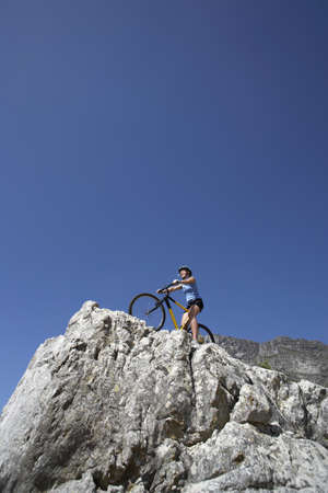 sitt: Female mountain biker sitting on bicycle at edge of rock, looking at view, low angle view