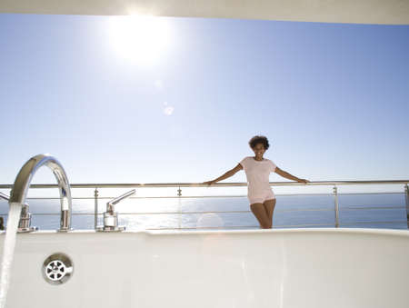 lavishly: Young woman standing on balcony by sea, smiling, portrait, bath in foreground LANG_EVOIMAGES
