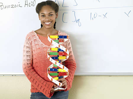 stood up: Teenage girl (15-17) standing beside whiteboard in classroom, holding DNA model, smiling, portrait