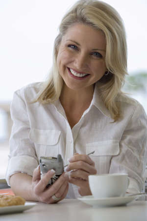 electronic organiser: Businesswoman sitting at table, using personal electronic organiser, smiling, front view, portrait LANG_EVOIMAGES