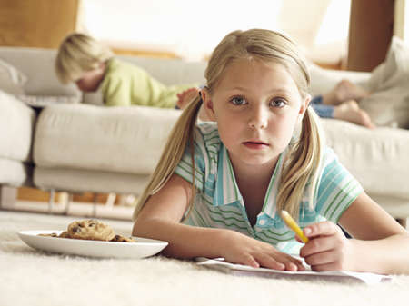caucas: Boy lying on sofa at home, focus on girl (6-8) lying on floor with paper and biscuits, surface level LANG_EVOIMAGES