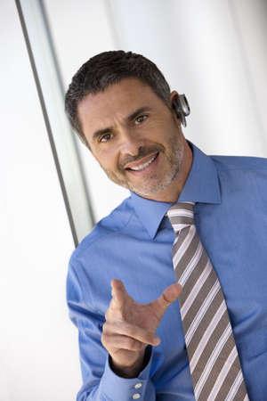 western european ethnicity: Businessman wearing mobile phone hands-free device, making hand sign, smiling, portrait (tilt) LANG_EVOIMAGES
