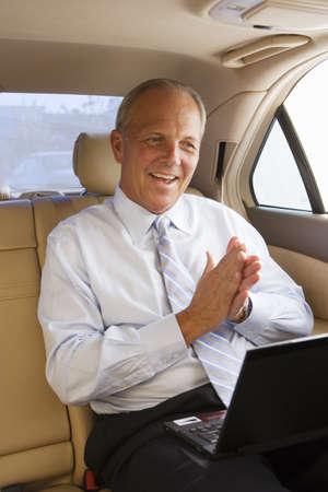 toils: Senior businessman sitting in back-seat of car, using laptop, rubbing hands with glee, smiling