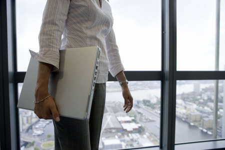 toils: Businesswoman standing beside window, carrying laptop underarm, side view, mid-section