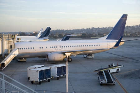 journeying: Stationary commercial aircraft at airport boarding gate, side view, elevated view