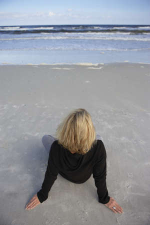 elevated view: Blonde woman wearing black jumper, sitting on sandy beach, looking at horizon over sea, rear view, elevated view (tilt)