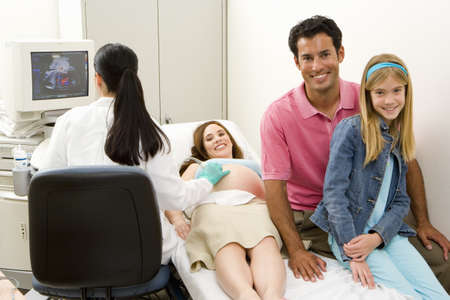 Pregnant woman having ultrasound scan with husband and daughter (9-11), smiling, portrait