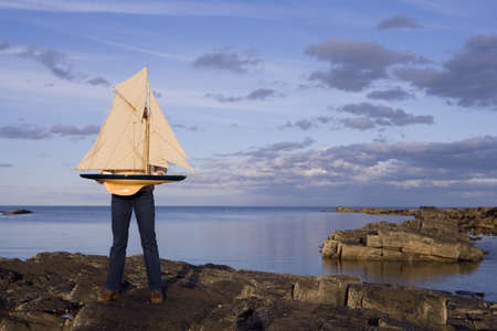 obscuring: Woman on rocks by sea, obscuring face with model boat LANG_EVOIMAGES