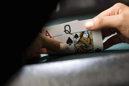 horizontals: Woman looking at playing cards at poker table, close-up of hands