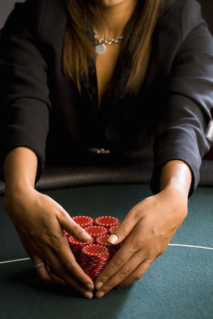 Woman collecting piles of gambling chips on table, mid section