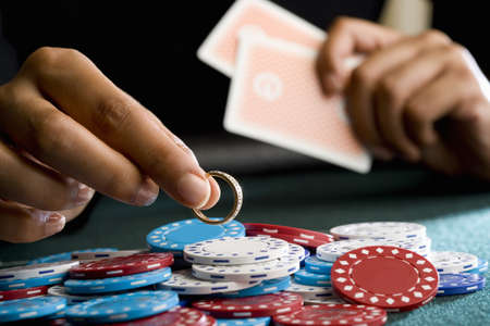 hope indoors luck: Woman placing ring on pile of gambling chips on table, mid section LANG_EVOIMAGES