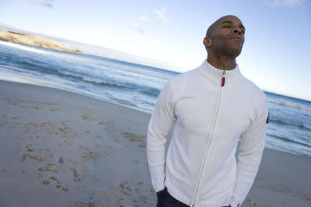 activ: Young man with eyes closed on beach, hands in pockets LANG_EVOIMAGES
