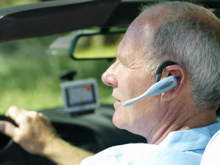 hands free device: Man with hands-free device in car, side view