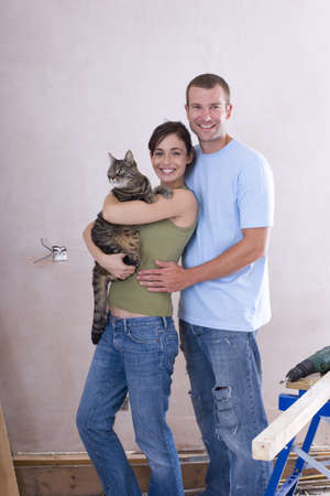Young couple, woman with cat, smiling, portrait