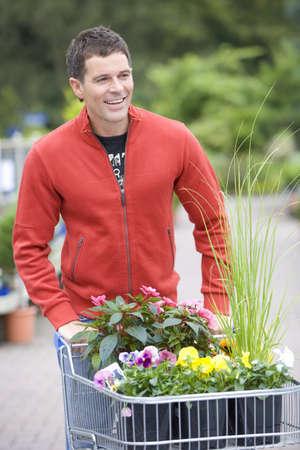garden center: Man with plants in garden center, smiling