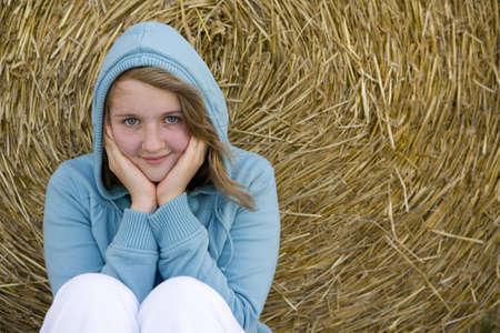 horizontals: Teenage girl (16-18) in hood by bale of hay, smiling, portrait LANG_EVOIMAGES