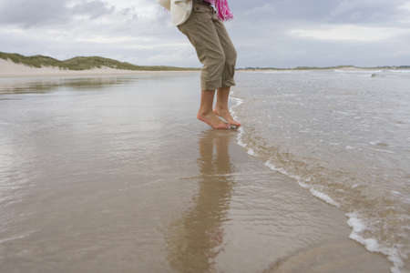 horizontals: Woman paddling in sea, low section