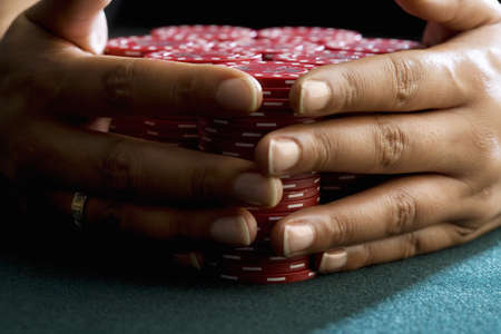 Woman with hands around piles of gambling chips on table, close-up of hands